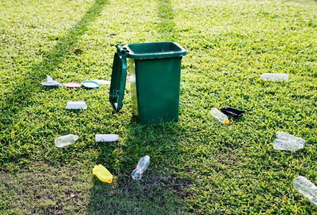 rubbish cluttered outside a trash bin