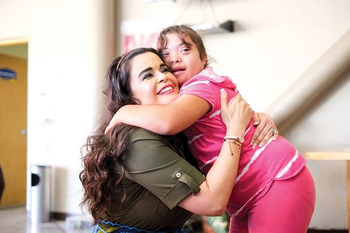 child with down syndrome being carried by her mother