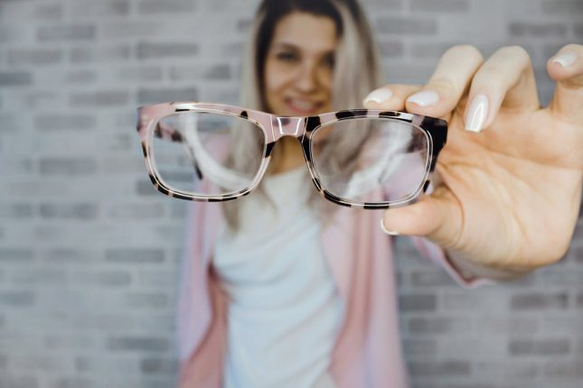 woman holding a pair of glasses