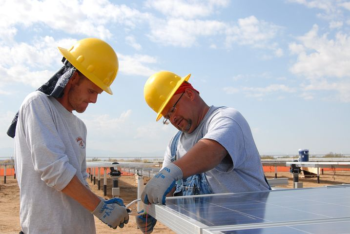 Two workers installing commercial solar panels